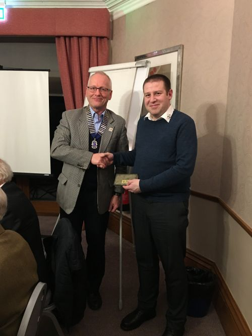 Lion Richard High receiving the Peter Taylor braces at the March business meeting from Lion President Phil Hassell